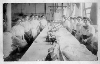 Women employees of the Reliance Waist Co. pose around a work table.