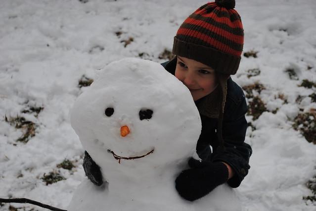Eli hugs the snowman