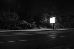 Billboard (andersdenkend) Tags: street trees blackandwhite bw snow wet lines dark advertising glow angle wide billboard schild asphalt werbung advertisment pitchblack weitwinkel werbetafel nikkor24mmf28 nikond700
