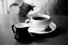 Black and White (La Branaro) Tags: blackandwhite bw stilllife film coffee austin restaurant 1 texas dof hand drink kodak bokeh beverage olympus depthoffield 35mmfilm shallow om creamer om1 125 asti trattoria 125px px coffeeandcream plusxfilm astitrattoria