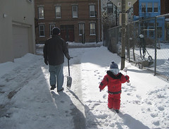 Dad and toddler walk in the snow, shovels in hand