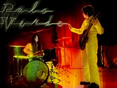 The two women of Palo Verde wear yellow suits. One plays a guitar and one is behind a drum kit.