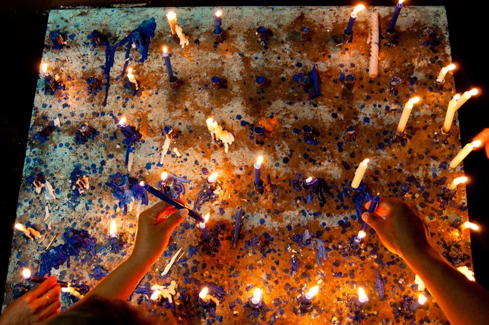 Devotos de la Virgen encienden sus velas en este repositorio de velas en la Capilla adjunta al Ycuá (Fuente de agua natural) a pocas cuadras de la Basílica. Muchas personas después de hacer sus oraciones reflexionan en la capilla y luego obtienen un poco de agua del Ycua que en la tradición se afirma que esta agua está bendecida por la misma Virgen de Caacupé. (Elton Núñez - Caacupé, Paraguay)