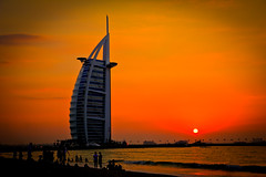 The Burj al-Arab, at sunset (modenadude) Tags: ocean city sunset orange sun 3 building tower love beach beautiful beauty architecture photoshop canon is persian amazing sand dubai gulf cross gorgeous muslim islam famous uae icon adobe sail usm drama vignette luxury f28 unitedarabemirates hdr controversy burj lightroom alarab 1755 emirati photomatix 550d cs5 thatsalotoforange t2i
