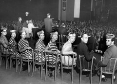 Women dressed in prison uniforms sitting on st...