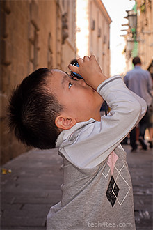 Boy pointing a camera upwards