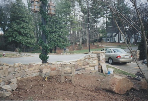 center stone wall connecting two stone columns under construction in Raleigh, North Carolina
