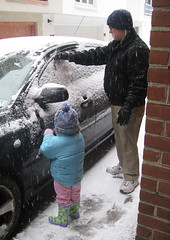 little girl and dad sweep snow off a black car