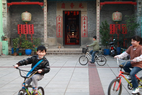 kids cycling in front of a temple in Macau