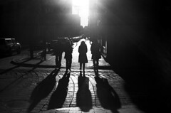 the four SHADOWS (brownbeatle) Tags: street city light shadow people sun silhouette dark downtown walk streetphotography providence cobblestone strong subject kodakbw400cn yashicaelectro35gsn contast ruckenfigur coloryashinondx45mmf17