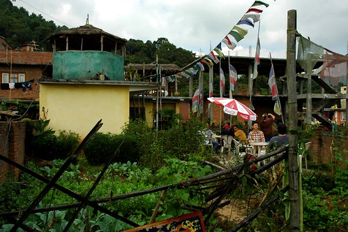 Enclosed garden, Sakya Lamdre Sangha at lunch, under a red and white Coca-cola umbrella, rural buildings, prayer flags, fence, Vajrayogini Restaurant, Pharping, Nepal by Wonderlane