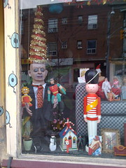 A detail of the left-hand side of the Upholstery Shop window. In the window are a cadaverous dummy wearing a suit and checkered tie, topped with a headdress made from a conical tinsel Christmas tree. Seated on the dummy's extended left arm is a Robin superhero doll; on its right arm is Lisa Simpson. In the foreground is a small model of a church, completed with steeple. Straddling atop the church is a female superhero. Beside the church, and much taller (about 2 feet tall) is a toy soldier figure.