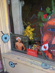 The bottom left corner of the Upholstery Shop window, containing a small red sign saying XXXmas, and a photo of a very buff shirtless dude in a Santa hat. More permanent fixtures in the window include a tribal-style mask, some geraniums and fake flowers, and Canadian flag.