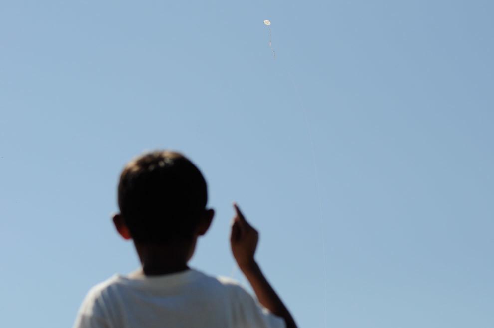 """Un Niño se entretiene haciendo volar su pandorga en el bañado Tacumbú mientras los chicos de """"Un techo para mi país"""" estaban construyendo su nuevo hogar. (Elton Núñez - Asunción, Paraguay)"""