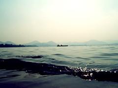 (toby.harvard) Tags: china water sailboat photography boat fishing sailing shoreline wave photograph shore sail hangzhou gleam watersedge shimmer lowangle tobyharvard