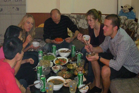 Foreign friends enjoying a traditional Tet meal with a Vietnamese family