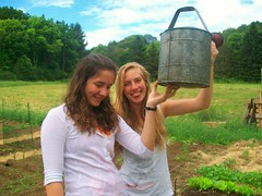 Julia and Sydney watering vegetables in our community garden