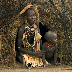 Karo tribe mother and kid coming out from the hpuse - Omo valley Ethiopia (Eric Lafforgue) Tags: africa travel portrait people baby childhood kara collier necklace kid artistic couleurs african decoration tribal bijou adventure mais ornament blackpeople omovalley bodypainting ethiopia tribe ethnic rite enfant karo motherandson jewel ethnicity headdress adornment coiffure afrique pigments headwear headgear tribu ethiopian omo eastafrica abyssinia ethiopie blackskin tribalportrait colorpicture ethnique abyssinie ethnie omoriver photocouleur mereetfils kolcho afriquedelest nomadicpeople colourpicture korcho hairness cluleur valleedelomo mereetenfant peoplesoftheomovalley 06204