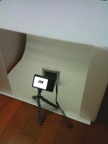 撮影ボックスによる撮影風景を撮影。iPhoneだから画質がイマイチだなぁ。カメラを撮るためのカメラが欲しくなるわ。