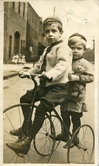 Two boys on a tricycle (c.1910) (pellethepoet) Tags: street girls boys bicycle kids children teddy tricycle postcard photograph teddybear pinafore azo rppc realphotopostcard