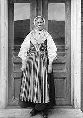 Greta Persson, Almo, Dalarna, Sweden (Swedish National Heritage Board) Tags: woman standing costume thirties 1930s stripes apron doorway older farmer bonnet dalarna 1935 folkcostume riksantikvariembetet theswedishnationalheritageboard