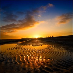 Evening light at Pett Level (adrians_art) Tags: sea sky cloud mist beach water reflections evening coast sand horizon cliffs hills shore sunburst ripples eastsussex englishchannel groynes cliffend pettlevels whichelsea