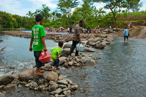 Warga Girimulyo menyebrangi sungai kayangan membawa makanan nasi berkat untuk disantap bersama pada upacara adat Kembul Sewu Sedulur