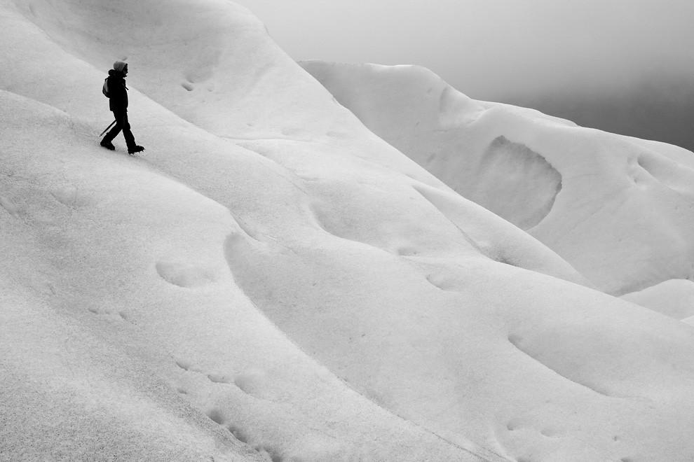 Un alpinista guía se aparta del grupo para verificar que el camino sea seguro, y los turistas podamos volver sanos. (Guillermo Morales -  Patagonia, Argentina)