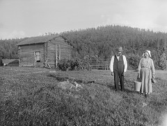 Mr and Mrs Persson, Dalarna, Sweden (Swedish National Heritage Board) Tags: portrait woman man field standing forest outdoors thirties 1930s bucket farm husband logcabin wife bonnet riksantikvariembetet darlarna theswedishnationalheritageboard