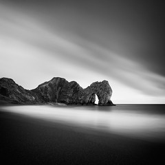 Sea Serpent (Andy Brown (mrbuk1)) Tags: ocean longexposure cloud seascape reflection beach water rock contrast landscape mono blackwhite surf arch fineart shingle dramatic wave diagonal ridge shore dorset geology iconic lulworthcove durdledoor jurassiccoast nd110