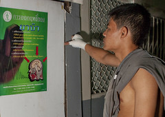 Muay thai boxer reading a warning poster before fighting - Bangkok Thailand (Eric Lafforgue) Tags: color colour sport thailand fight asia bangkok capital culture tailandia thalande asie capitale tradition backstage siam thailandia couleur muaythai thailande violent thaiboxing  coulisse  tayland   muangthai tajlandia photocouleur thaifld      thai6129