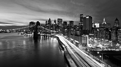 Downtown Manhattan (tamjty) Tags: city nyc longexposure nightphotography light sky urban blackandwhite bw usa ny monochrome skyline night clouds america canon buildings photography eos us downtown cityscape skyscrapers manhattan tripod 7d manhattanbridge lighttrails 1022mm citynights f3545 brookylnbridge