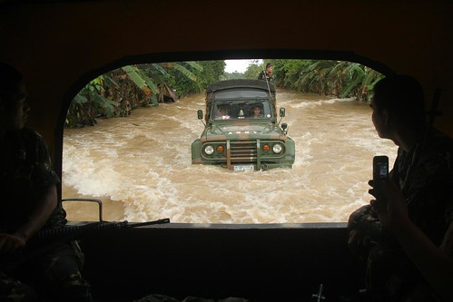 A military convoy carrying relief goods navigates through the flooded national highway on Thursday at Barangay San Roque in Kitcharao, Agusan del Norte. Elements of the Charlie Company of the 30th Infantry Battalion transported relief goods from Butuan City to Mainit town, also in Agusan del Norte. Mindanews Photo by Keith Bacongco