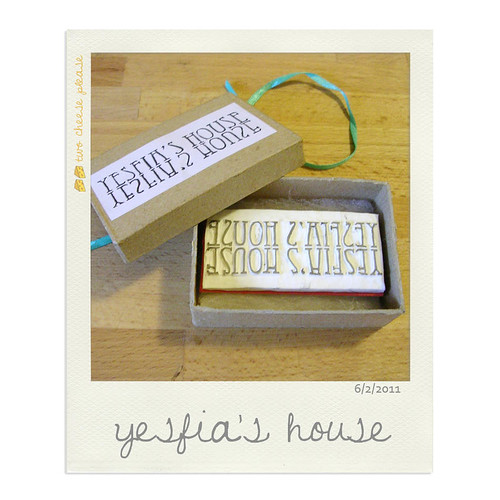 """Custom hand carved stamp sitting in a brown kraft recycled gift box. Stamp reads """"Yesfia""""s House"""""""