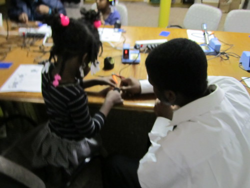 "Elishah helping a younger solderer • <a style=""font-size:0.8em;"" href=""http://www.flickr.com/photos/52992303@N05/5468978840/"" target=""_blank"">View on Flickr</a>"