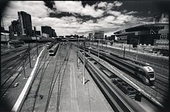railyard landscape (mugley) Tags: city sky urban blackandwhite bw slr film lines skyline architecture modern clouds rollei 35mm buildings prime nikon cityscape skyscrapers stadium towers grain perspective tracks railway australia melbourne wideangle trains victoria scan tokina lookdown negative epson docklands 135 vignetting r3 urbanlandscape redfilter rhs railyards telstradome f801s polariser latrobest 25a v700 keystoning rolleir3 neo200 tokina17mmf35atx docklandsstadium 120spencer etihadstadium spencerstrailyards rolleihighspeed