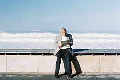 The Old Man and the Sea (Miguel Pires da Rosa) Tags: sea film portugal analog 50mm reading iso100 newspaper oldman olympus boardwalk zuiko om2 solaris focomanual espinho idoso 2011 ferrania om2sp mpires miguelpires mpiresdarosa
