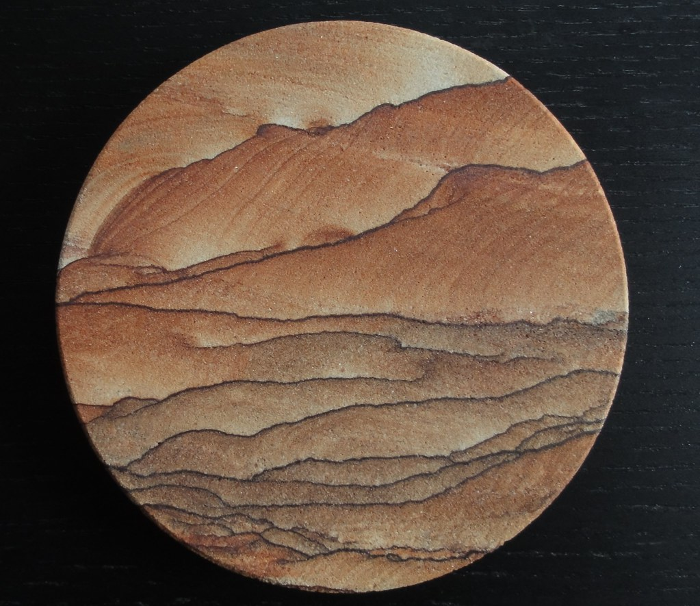 Image shows a round coaster on a black wood background. It's variations of brown, russet, and tan. It looks like someone's painted a mountainous desert landscape complete with foothills on it, but it's all natural.