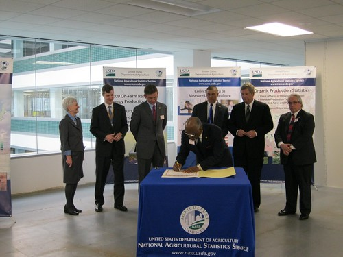 """St. Louis County Executive Charlie A. Dooley signing the dedication certificate at the celebration of the new national operations center for USDA's National Agricultural Statistics Service in Overland, Mo. He was joined by NASS Administrator Dr. Cynthia Clark, GSA Regional Administrator Jason Klumb, Missouri Director of Agriculture Jon Hagler, U.S. Rep. William ""Lacy"" Clay, Jr., U.S. Agriculture Secretary Tom Vilsack, and Overland, Mo. Mayor Michael Schneider."""