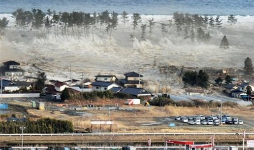 Waves of tsunami hit residences after a powerful earthquake in Natori, Miyagi prefecture (state), Japan, Friday, March 11, 2011.  The largest earthquake in Japan's recorded history slammed the eastern coast Friday. (AP Photo/Kyodo News) JAPAN OUT, MANDATO