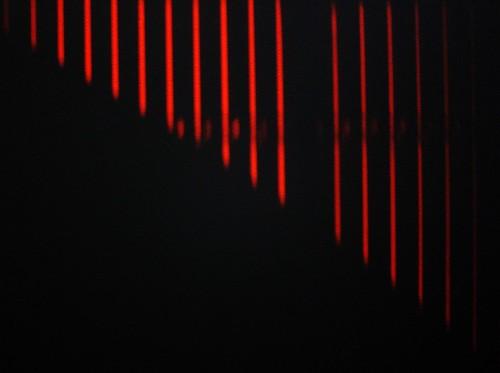 Burnt Orange Sunset Rays Through Window Blinds Onto Black Wall