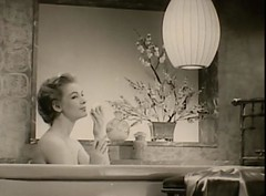 a black and white still of a white woman in a tub smelling soap