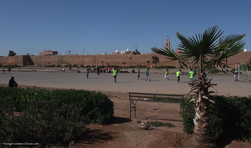 Des jeunes jouent au foot devant les murailles