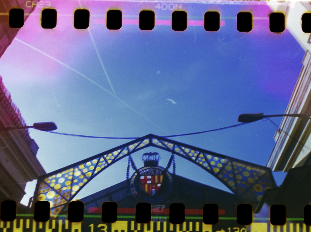 Home-scanned photo with sprocket holes of the main entrance of La Boqueria market in Barcelona.