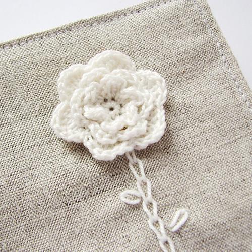crocheted flower on linen nedle book