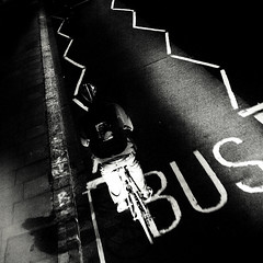 . (lazy_lazy_dog) Tags: road street blackandwhite bw man motion night contrast square cycling moving cyclist angle pov grain streetphotography commuting buslane