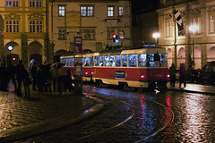 All Aboard the Night Tram (TheFella) Tags: street blue light red people slr wet rain yellow night digital canon reflections eos photo europe czech prague tram praha unescoworldheritagesite unesco nighttime stop photograph processing czechrepublic dslr streetcar umbrellas tramlines tatra postprocessing 500d malstrana nighttram