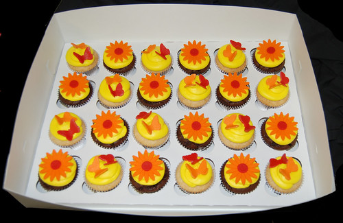 yellow orange and red cupcakes topped with butterflies and daisies box