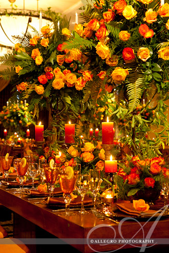 david-tutera-my-fair-wedding-ny-book-details- orange yellow amber candles and roses with wood tables- caribbean flare wedding reception