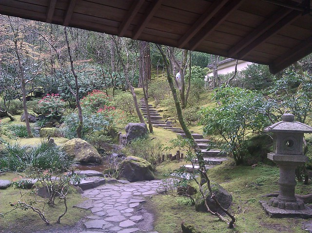 A path and steps of stone rise through peaceful green grounds from a sheltering pavillion at the Japanese Garden